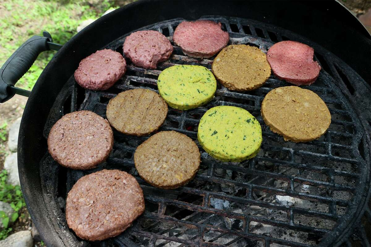 Several different brands of meatless burgers cook on the grill at Chuck's Food Shack for a taste test.