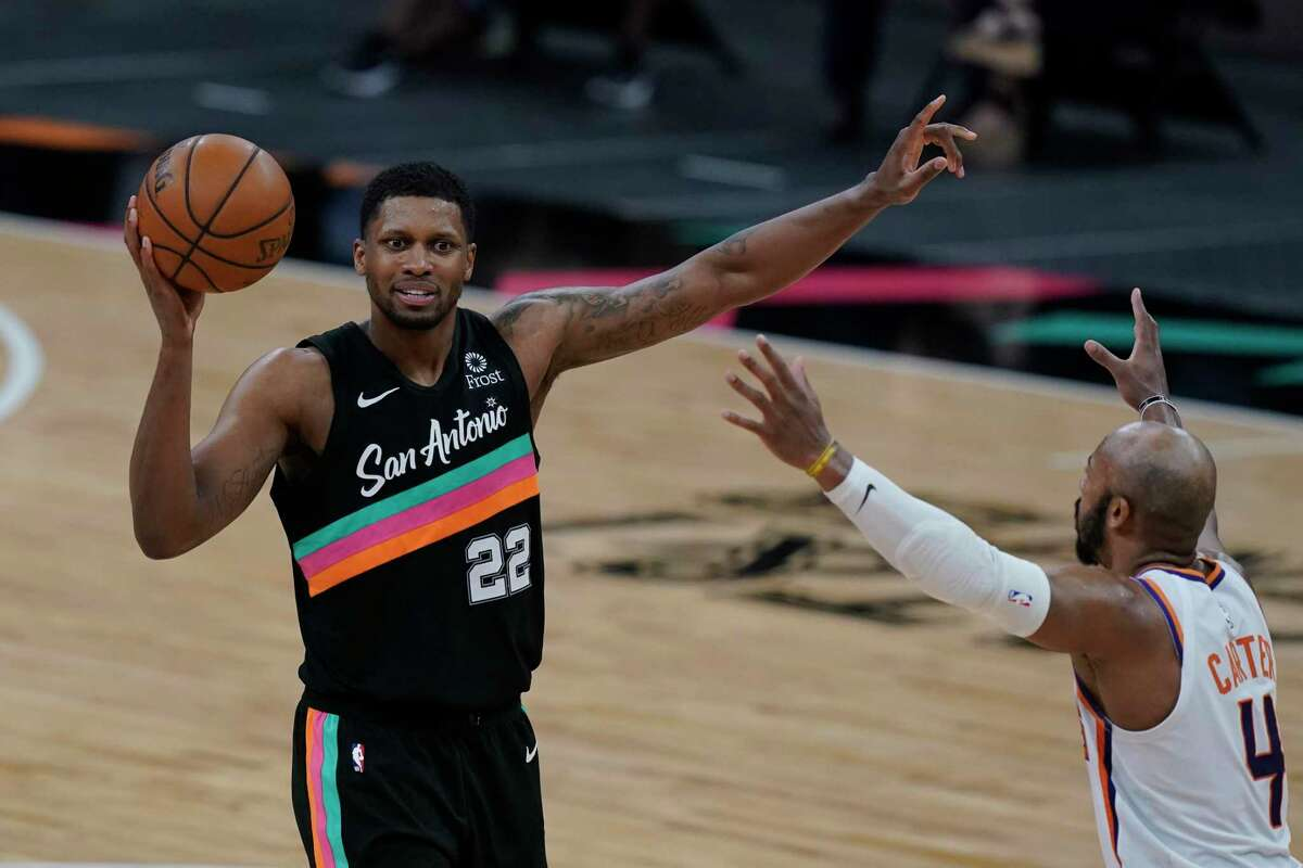San Antonio Spurs forward Rudy Gay (22) looks to pass around Phoenix Suns guard Jevon Carter (4) during the second half of an NBA basketball game in San Antonio, Sunday, May 16, 2021. (AP Photo/Eric Gay)