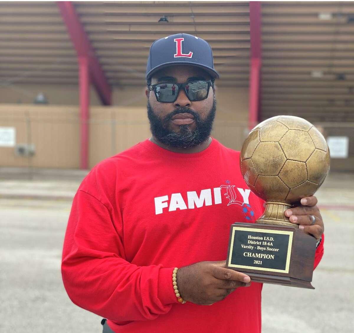 Lamar Texans boys soccer coach Jeremy Davison holds the District 18-6A championship trophy