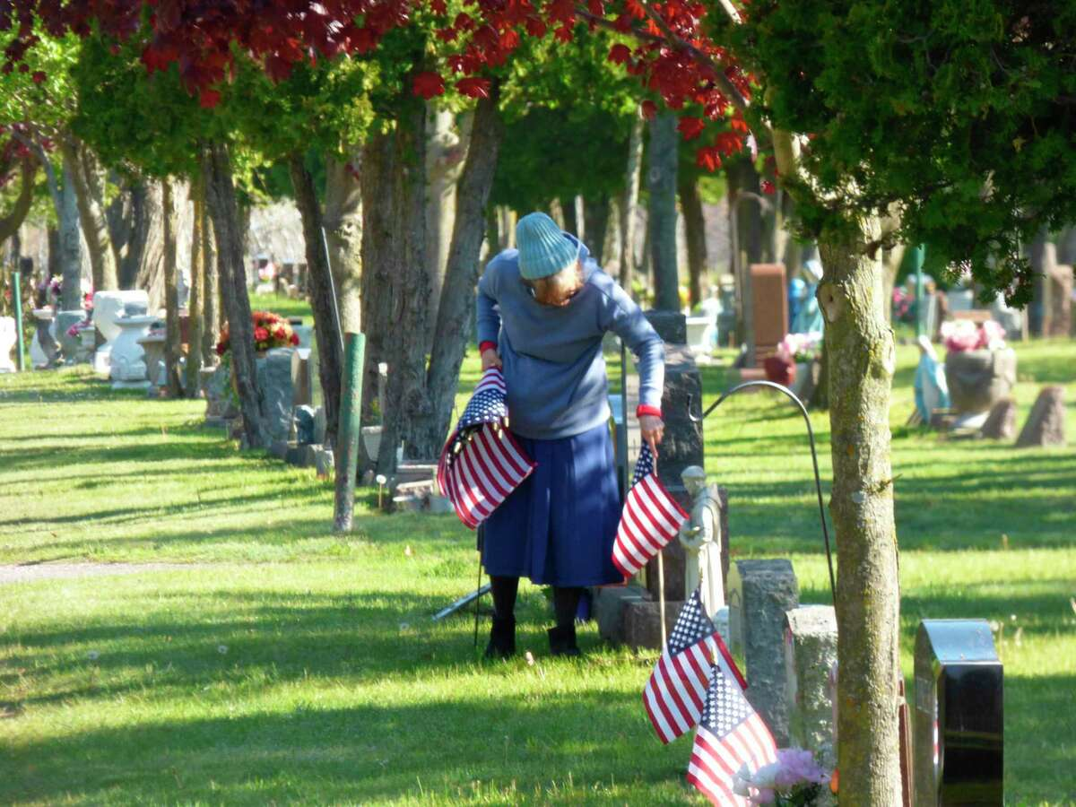 A volunteer plants a row of flags at MountCarmel Cemetery in Manistee. (Scott Fraley/News Advocate)