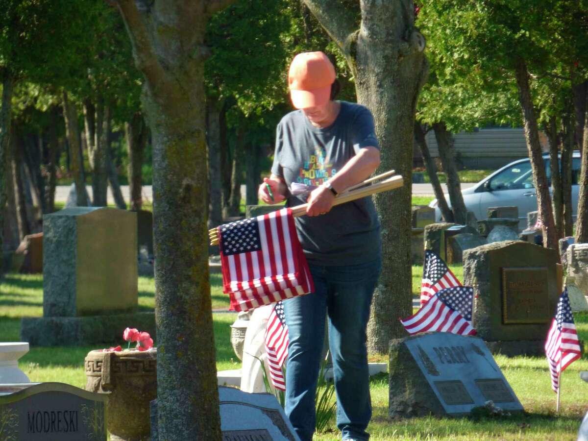 Volunteers place flags on graves of veterans in Manistee ahead of Memorial Day weekend. (Scott Fraley/News Advocate)