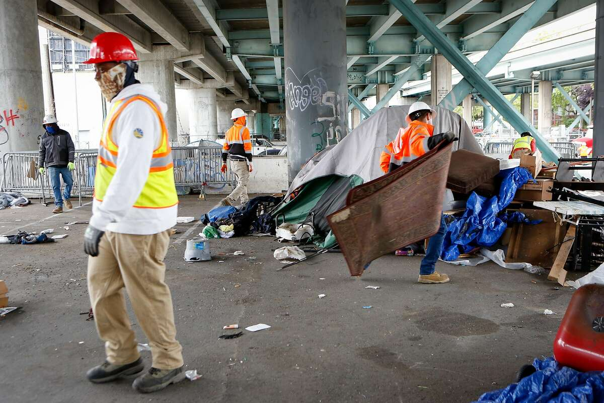 Workers from CalTrans clear items at the Merlin Street encampment just before a sweep performed by California Highway Patrol and CalTrans on Monday, May 17, 2021 in San Francisco, Calif.
