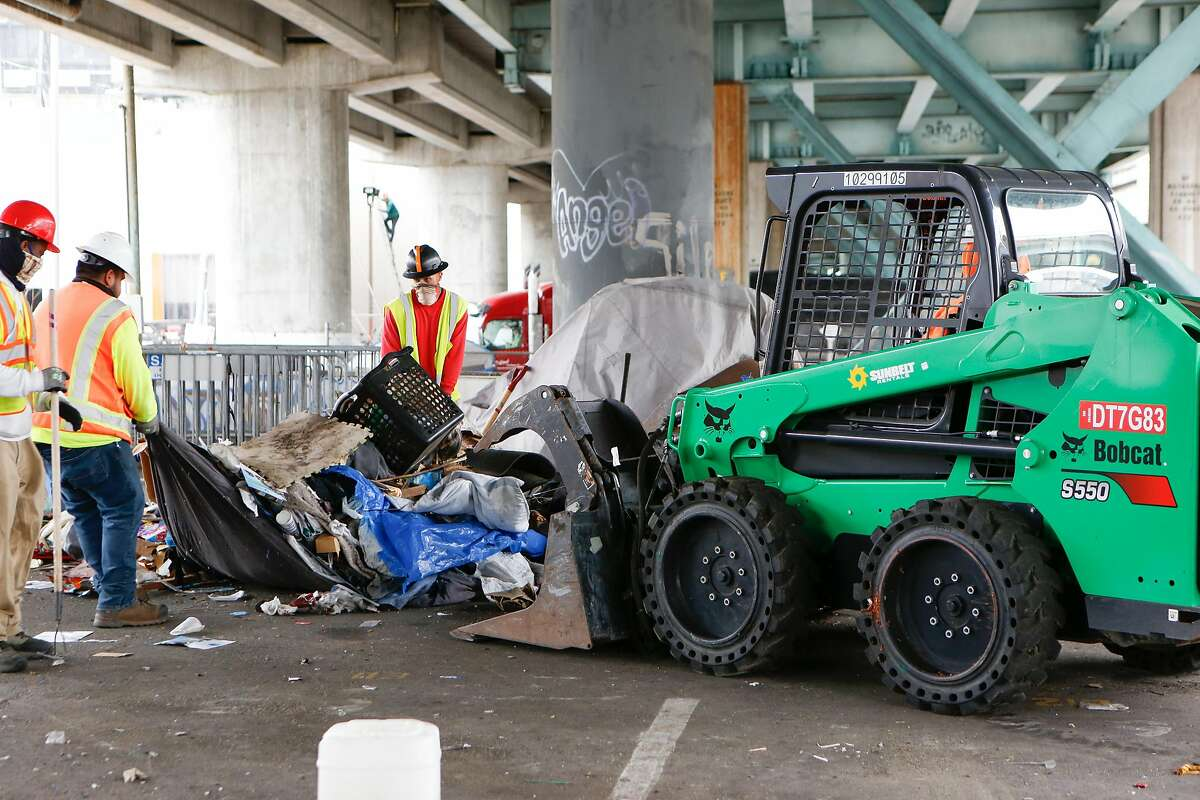 Workers from CalTrans clear items with the help of a front end loader at the Merlin Street encampment just before a sweep performed by California Highway Patrol and CalTrans on Monday, May 17, 2021 in San Francisco, Calif.