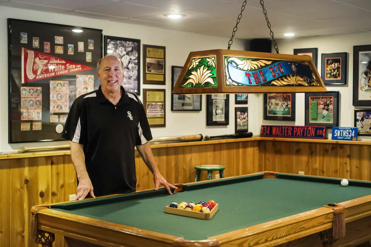 Rick Ohle poses for a portrait Thursday, May 13, 2021 in the basement of his Midland home, where his vast collection of Chicago sports memorabilia is housed. (Katy Kildee/kkildee@mdn.net)