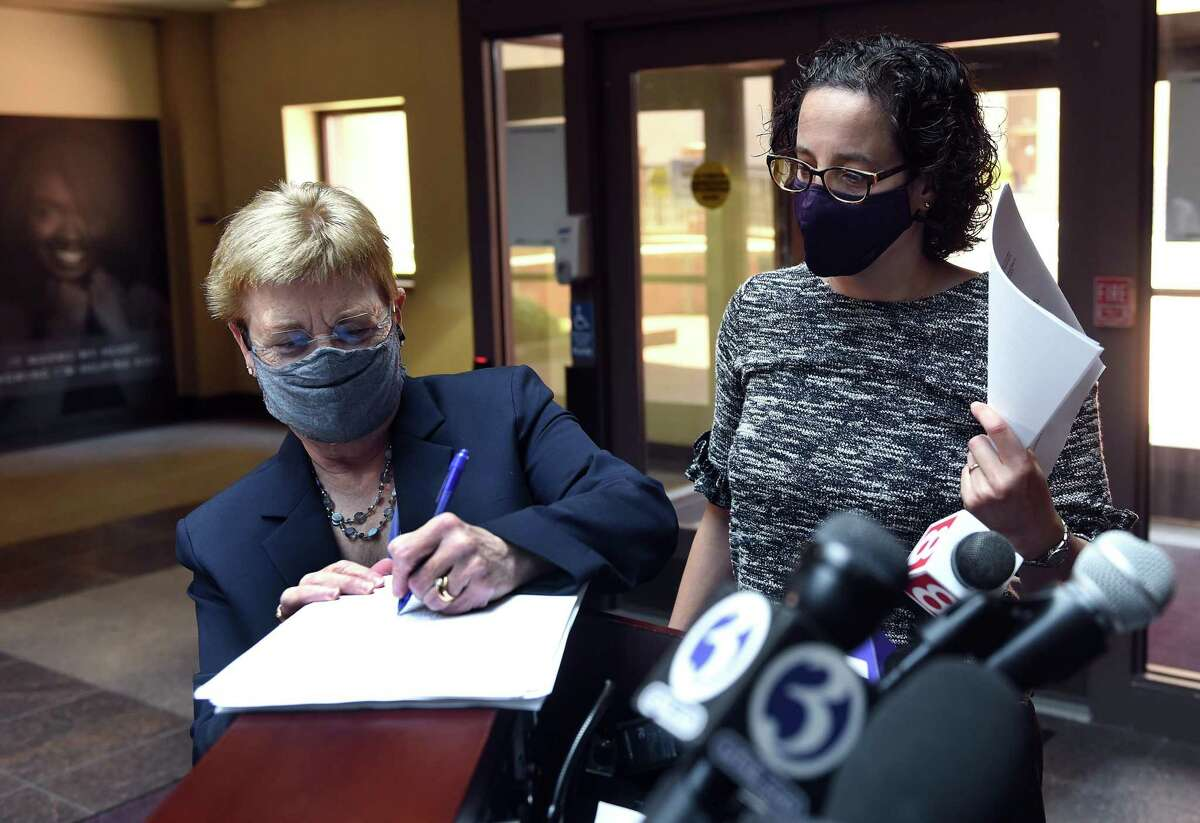 New Haven Legal Assistance Association attorney Amy Marx, right, watches New Haven Corporation Counsel Patricia King sign settlement papers of a lead inspection and enforcement program lawsuit before a press conference in City Hall in New Haven May 17, 2021.