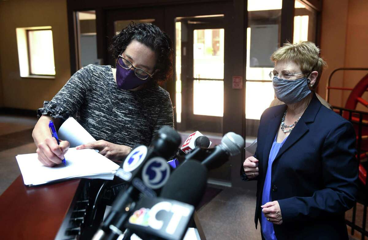 New Haven Corporation Counsel Patricia King, right, watches New Haven Legal Assistance Association attorney Amy Marx sign settlement papers of a lead inspection and enforcement program lawsuit before a press conference in City Hall in New Haven May 17, 2021.