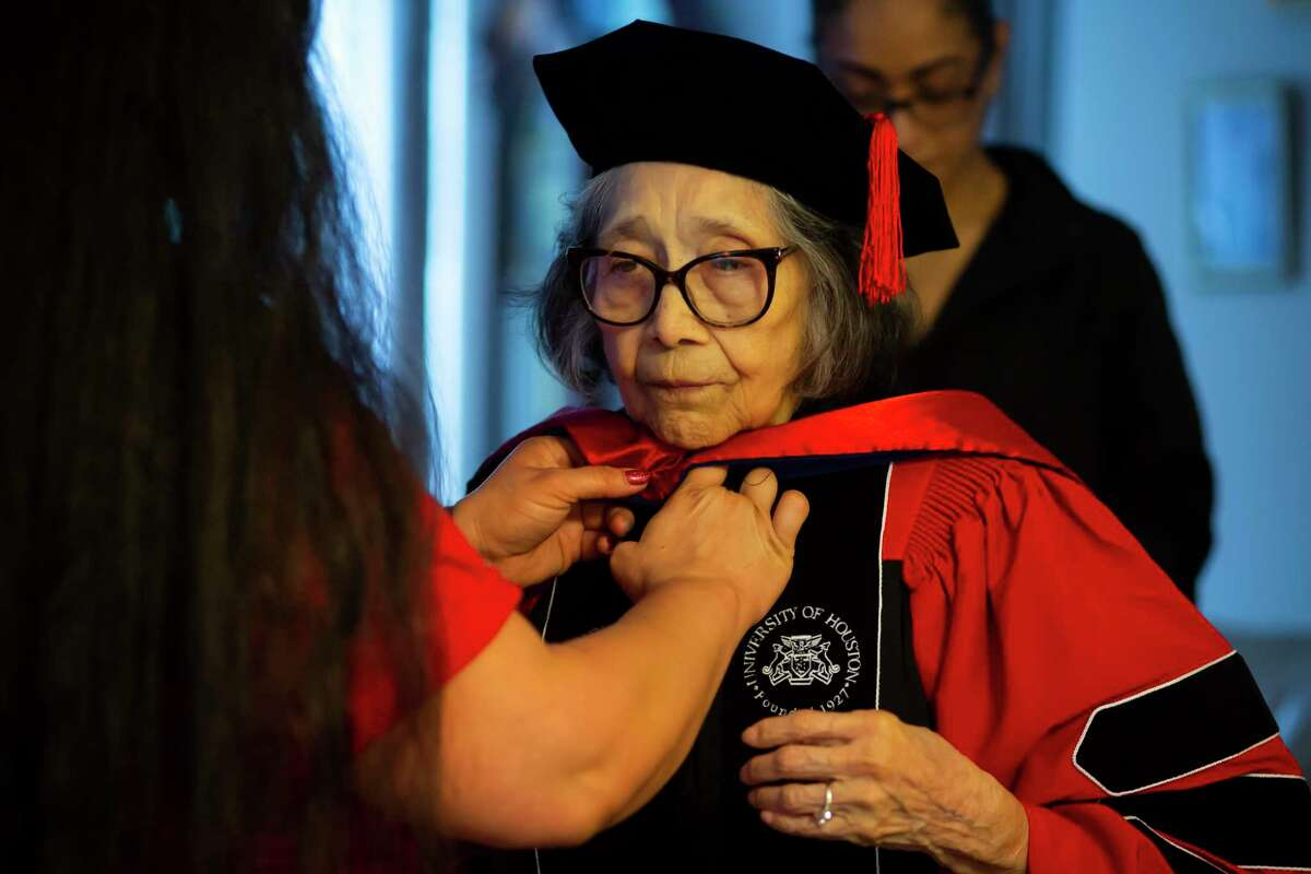 Jesse Goins helps her 90-year-old grandmother Esther Campos put on graduation robes during a virtual reception for Campos in her home on Sunday, May 16, 2021. Campos stopped just short of earning her PhD more than 40 years ago but will receive an honorary degree from the University of Houston after a lifetime of service to children and public education.