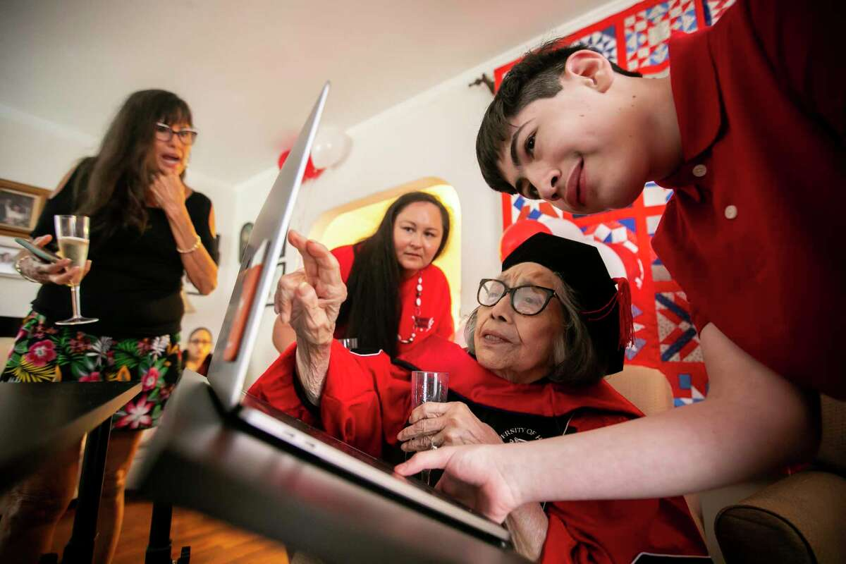 Daughter Olga Benz and granddaughter Jesse Goins help 90-year-old Esther Campos, along with Campos's 14-year-old great grandson David Romero, during a graduation reception in her home on Sunday, May 16, 2021. Campos stopped just short of earning her PhD more than 40 years ago but will receive an honorary degree from the University of Houston after a lifetime of service to children and public education.