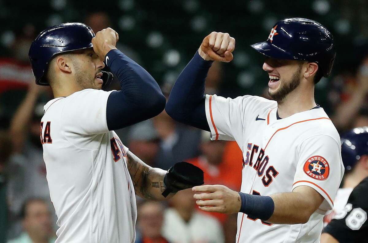 Having crossed the plate first, Astros shortstop Carlos Correa, left, congratulates Kyle Tucker after the right fielder's two-run homer against the Angels last Wednesday at Minute Maid Park.