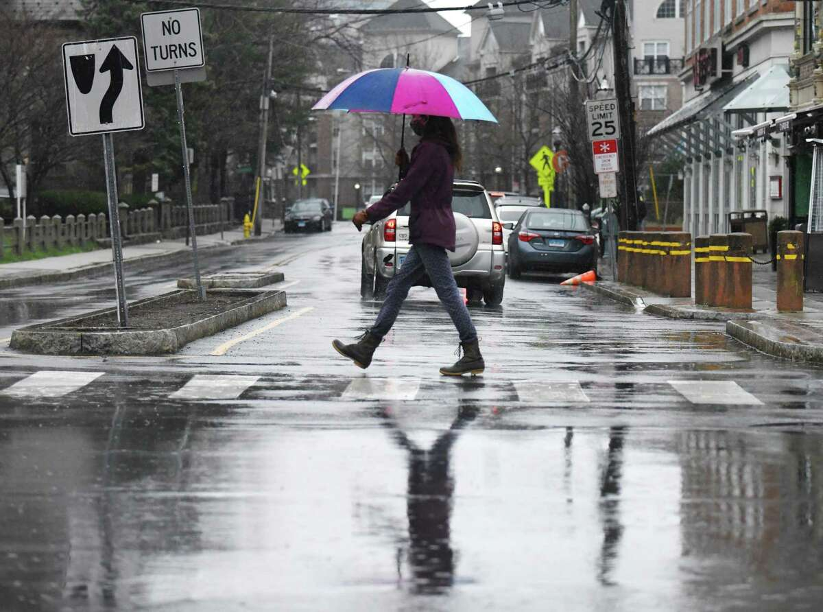 A woman crosses the intersection of Bedford Street and Forest Street as rain falls in Stamford, Conn. Sunday, March 28, 2021. Stamford received heavy rainfall Sunday morning before the storm tapered off in the afternoon.