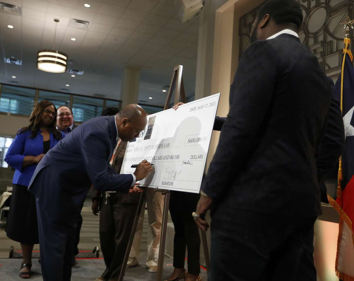 Mayor Sylvester Turner signs a giant check with Curtis