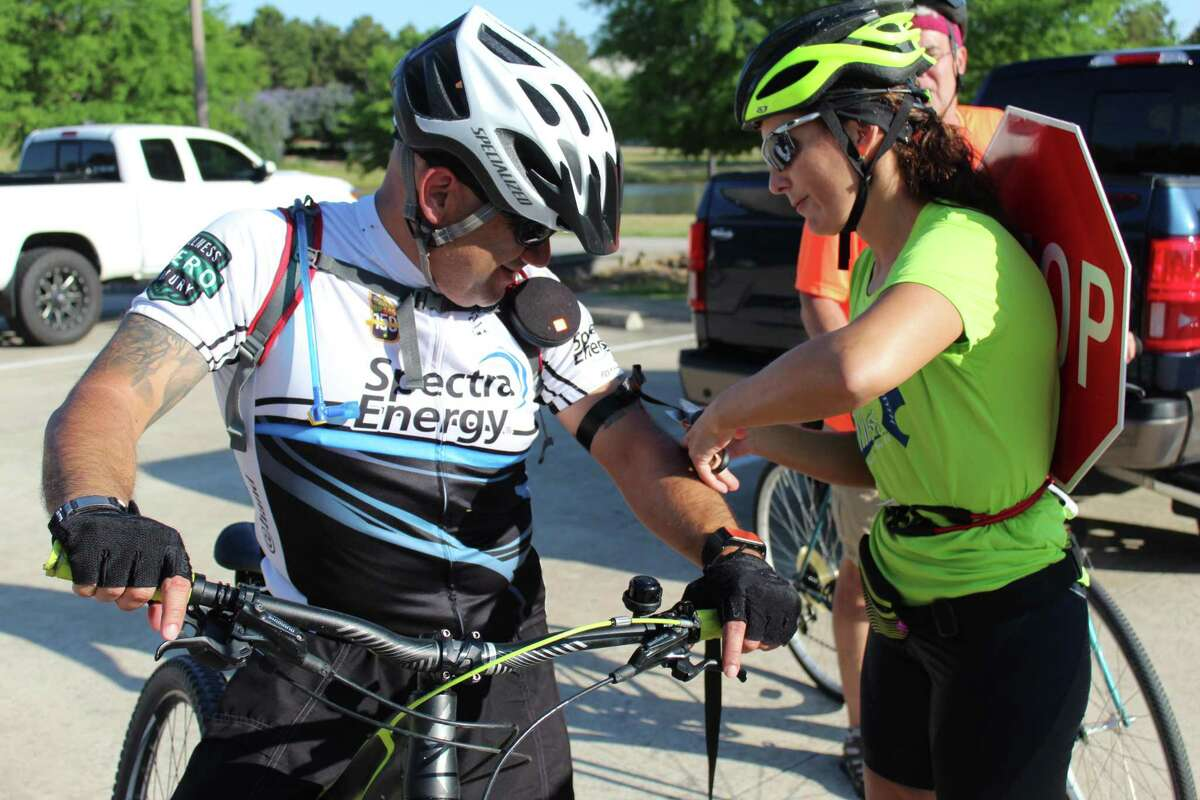 This year's Ride of Silence is Wednesday. During the ride, participants tie black ribbons on their arms to honor cyclists who have been injured or killed by a motorist. In this file photo, Fernanda Suarez, right, the former co-vice president of Bike The Woodlands, helps an attendee at the 2019 Ride of Silence.