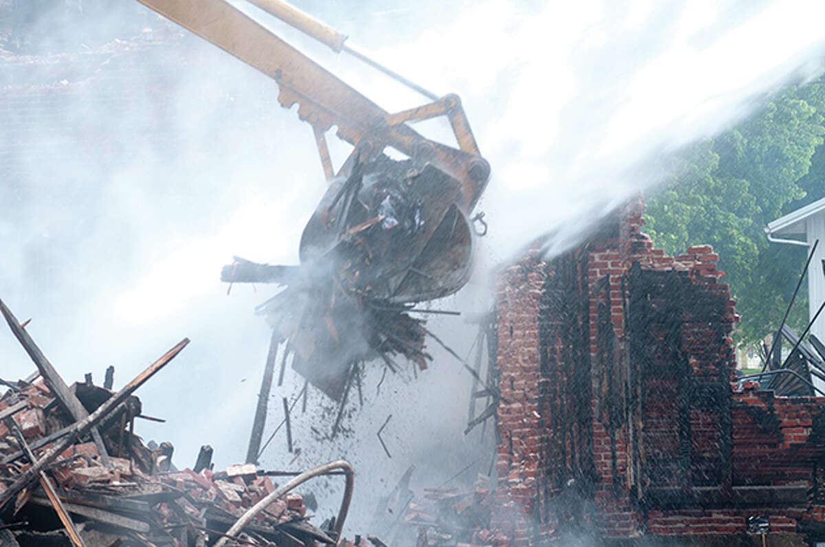 Demolition crews work on bringing down the building at 601 E. Fourth St. Monday after a fire broke out Sunday evening causing all 13 residents to be evacuated and injuring one resident and three firefighters.