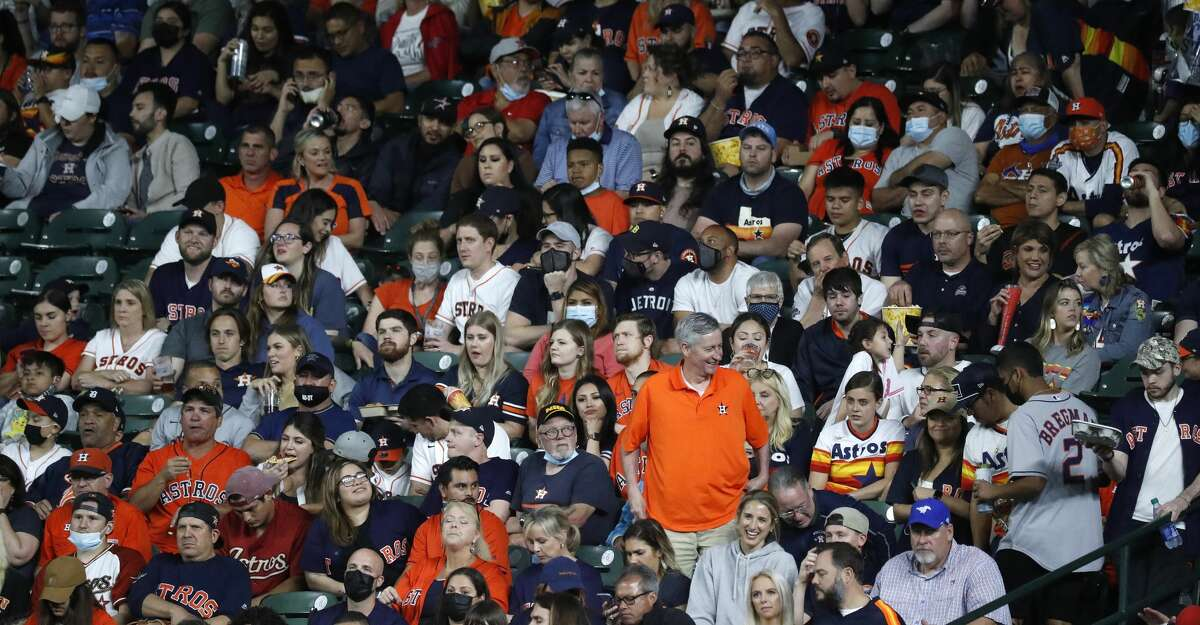 Fans masked and unmasked in the right field stands during the fourth inning of an MLB baseball game at Minute Maid Park, in Houston, Wednesday, April 14, 2021.