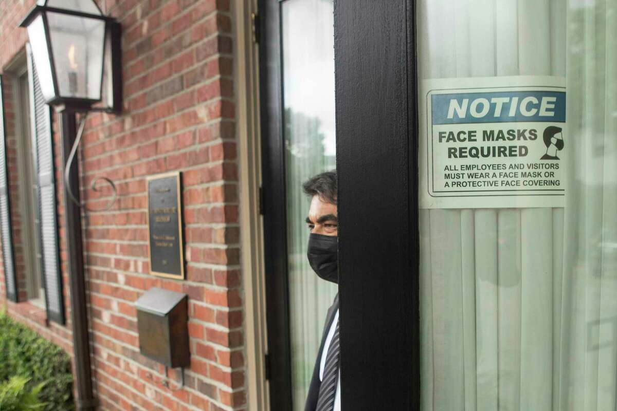 Horacio Santos opens to the door at Bradshaw-Carter funeral home to wait for a client Monday, May 17, 2021 in Houston. The funeral home still has signs posted on its doors requiring masks.