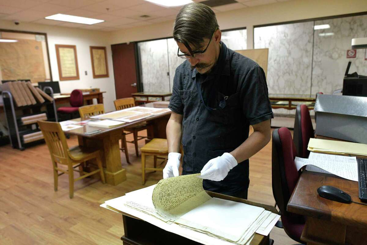 Archivist David Carlson looks through historic papers dating from the early 1800s in the Bexar County Spanish Archives collection. Bexar County leaders have suggested the county provide scholarly support for a planned Alamo museum, and on Tuesday will discuss a proposal to help fund the facility.