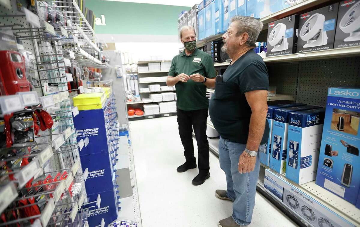 Customer Robert Turnbo, right, looks for a ceiling fan part without a mask on, as he was helped by Charles Plumb in the electrical area of Bering's Hardware and Gifts, Monday, May 17, 2021, in Houston. Story about how retailers are responding to revised CDC guidelines on masks. Bering's removed signs at its entrances saying masks are required, and increasingly more people are coming inside without them, its owner said.