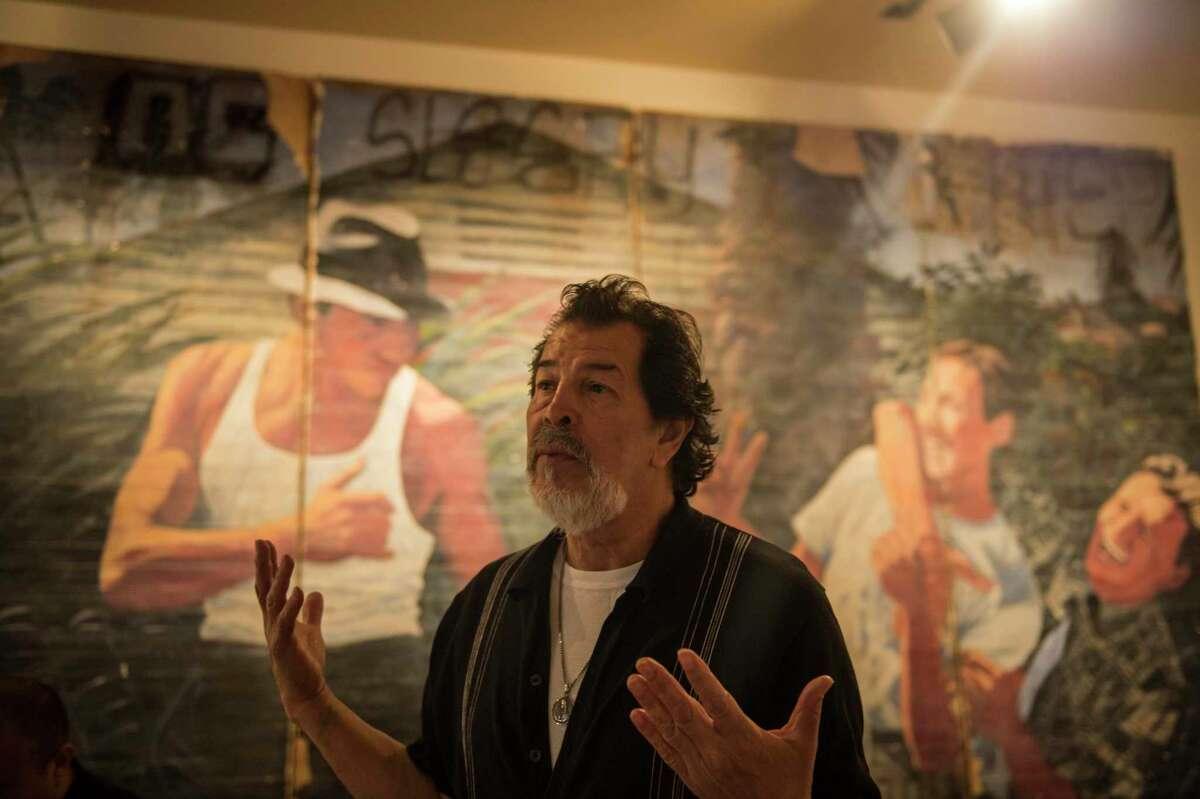 Artist Adan Hernandez stands in front of his mural