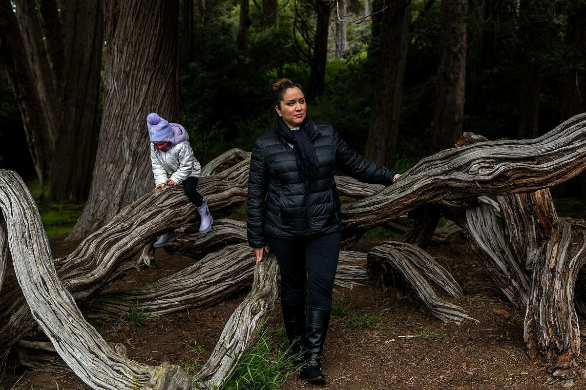 Lily Marquez stands for a portrait as four-year-old daughter Mia Goussen plays on a tree in Golden Gate Park in San Francisco, Calif., Monday, May 17, 2021.