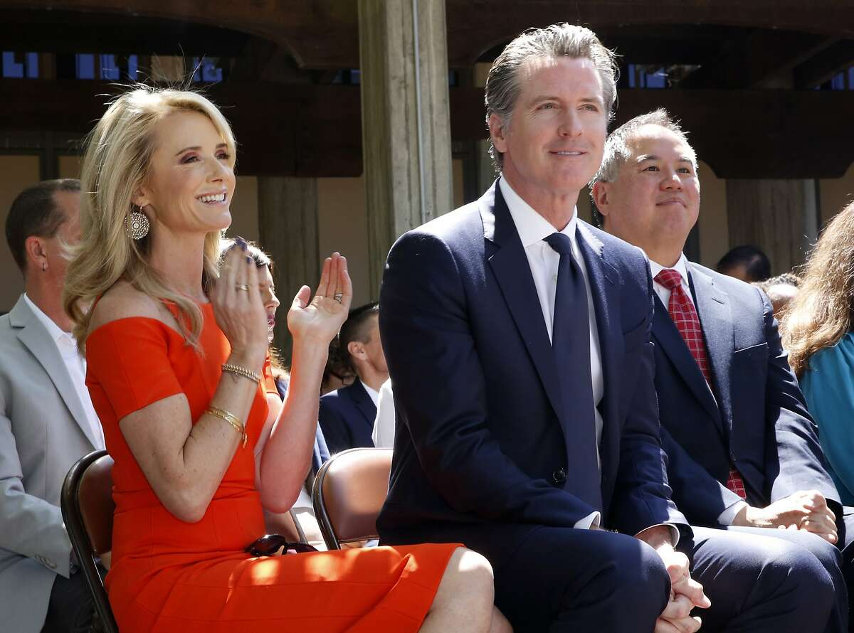 FILE -- In this July 1, 2019, file photo, First Partner Jennifer Siebel Newsom, left, attends a signing ceremony with her husband, Gov. Gavin Newsom, right, at Sacramento City College in Sacramento, Calif. The Newsoms made about $500,000 more in 2019, Gavin Newsom's first year as governor, than they did before, according to tax returns released on May 17, 2021. Newsom, a Democrat, has pledged to release his returns every year. (AP Photo/Rich Pedroncelli, File)