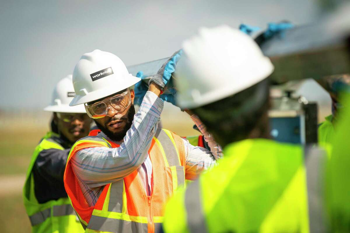 Quinton Buntin works to adjust a beam that will hold solar panels during a training class on installing the solar infrastructure, Tuesday, May 11, 2021, at a solar farm south of El Campo. Buntin has been working as a mechanic, but sees the solar energy industry as the job of the future.