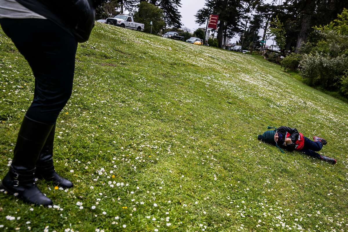 Lily Marquez (left) watches as son Jeremiah Goussen, 5, rolls on a grassy slope at Mother's Meadow in Golden Gate Park.