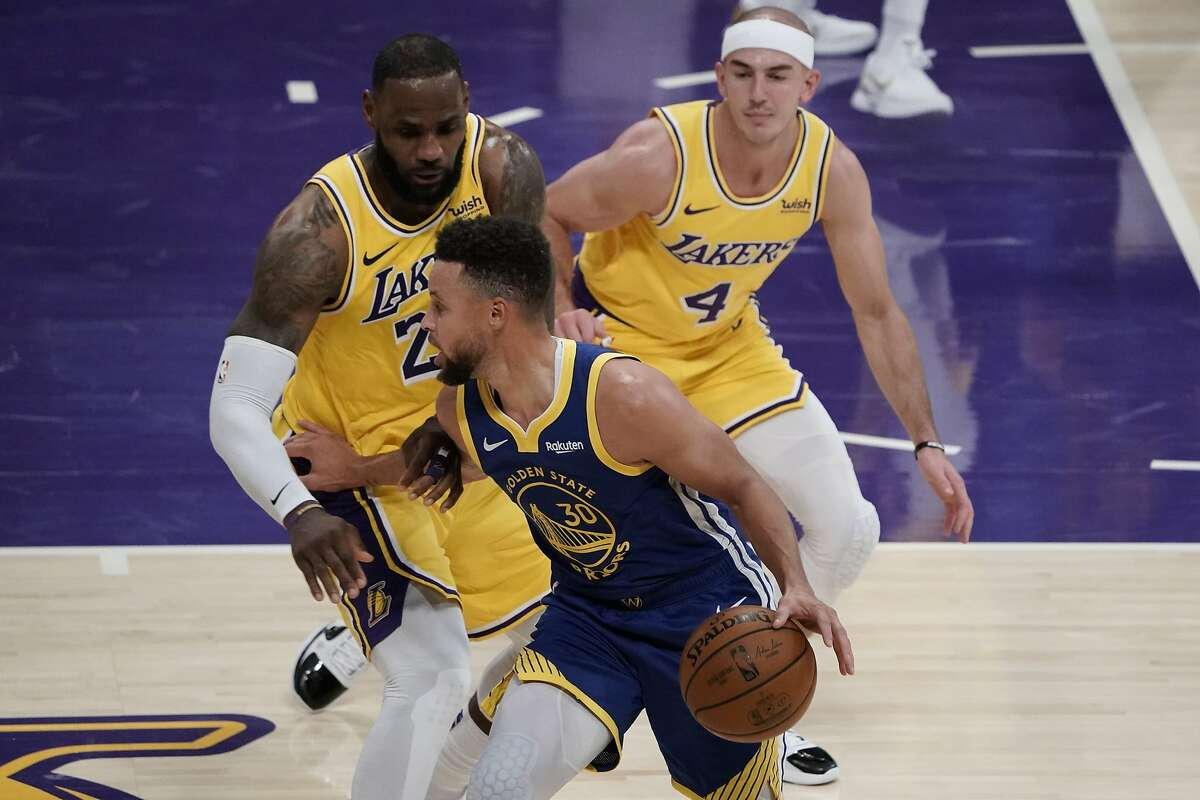 Los Angeles Lakers' LeBron James, left, pressures Golden State Warriors' Stephen Curry during the second half of an NBA basketball game, Monday, Jan. 18, 2021, in Los Angeles. The Warriors won 115-113. (AP Photo/Jae C. Hong)