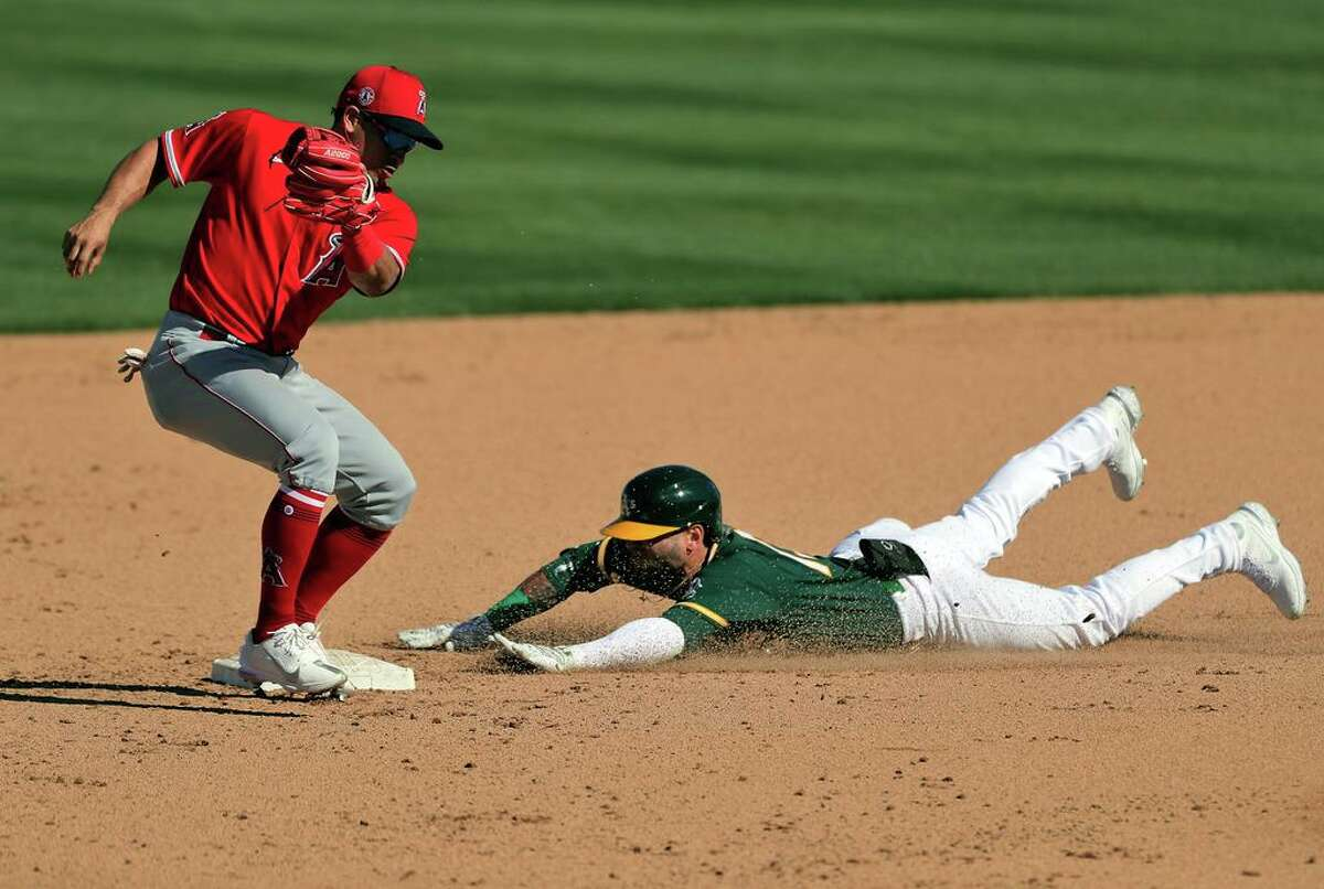 Luis Barrera (13) slides in safe to second on his double in the sixth inning as the Oakland Athletics played the Los Angeles Angels at Hohokam Stadium in Mesa, Ariz., on Friday, March 5, 2021.