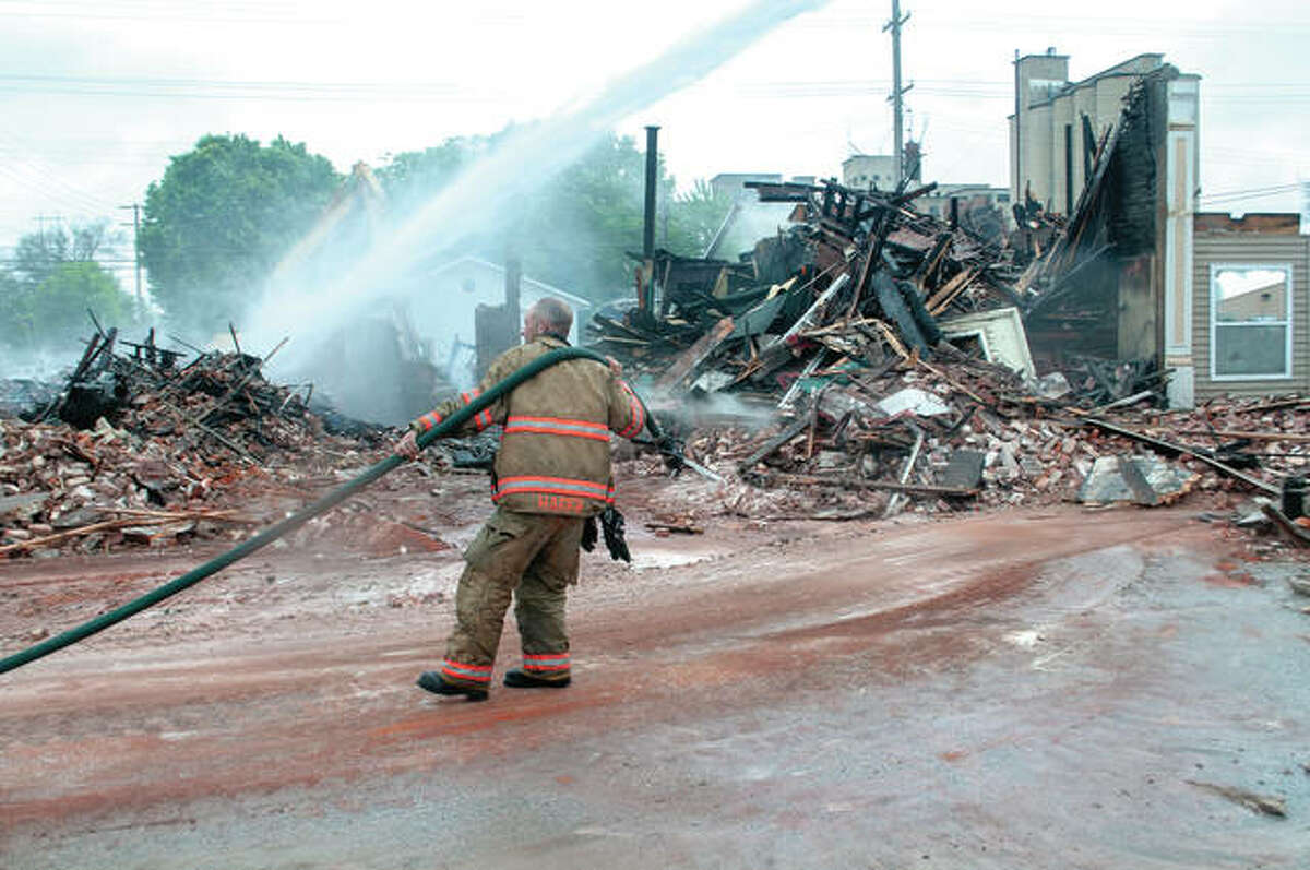 Brandon Hager, assistant fire chief for Beardstown Fire Department, drags a hose Monday while working to ensure a blaze didn't flare up as crews were working to demolish the building at 601 E. Fourth St. Several crews were called out Sunday evening by reports of fire and smoke. The cause of the fire has not been determined.