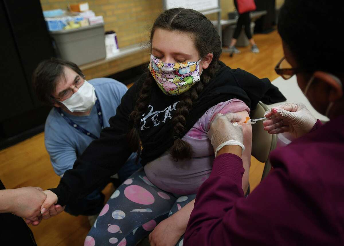 Kaitlyn Miniter, 12, of Milford, holds her mom's hand and dad Chris looks on as she receives the Pfizer Covid-19 vaccine from nurse Latrice Garcia.