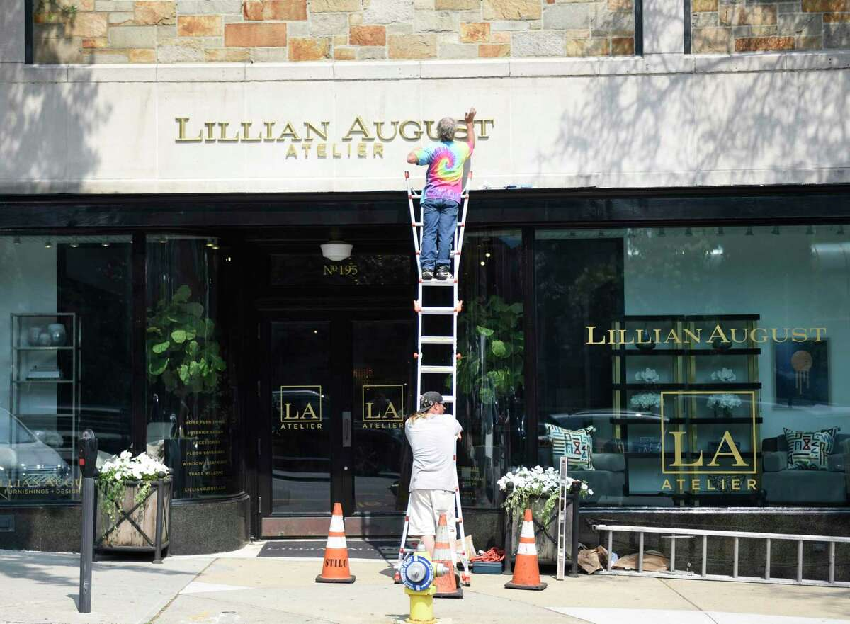 A crew puts up the lettering at the new location of Lillian August Atelier at 195 Greenwich Avenue in downtown Greenwich, Conn., Monday, June 18, 2018.