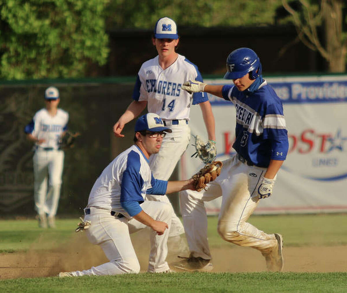 Marquette Catholic shortstop Braden Coles (left) looks to the umpire after applying a tag too late to get Freeburg's Lane Otten at second base while the Explorers' Joey Gatermann (14) backs up the play in a May 7 game at Hopkins Field in Alton.