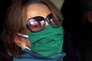 Carmen Davenport, sporting a holiday appropriate mask, as she waits for a free lunch of corned beef and cabbage, which were boxed up and handed out for a special St. Patrick's Day drive-thru luncheon at The Bigelow Center for Senior Activities in Fairfield, Conn., on Tuesday Mar. 16, 2021.