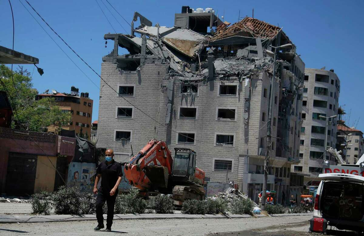 A Palestinian walks by a building hit by an Israeli airstrike in Gaza City on Tuesday. Since the fighting began last week, the Israeli military has launched hundreds of airstrikes it says are targeting Hamas' militant infrastructure, while Palestinian militants have fired thousands of rockets into Israel.