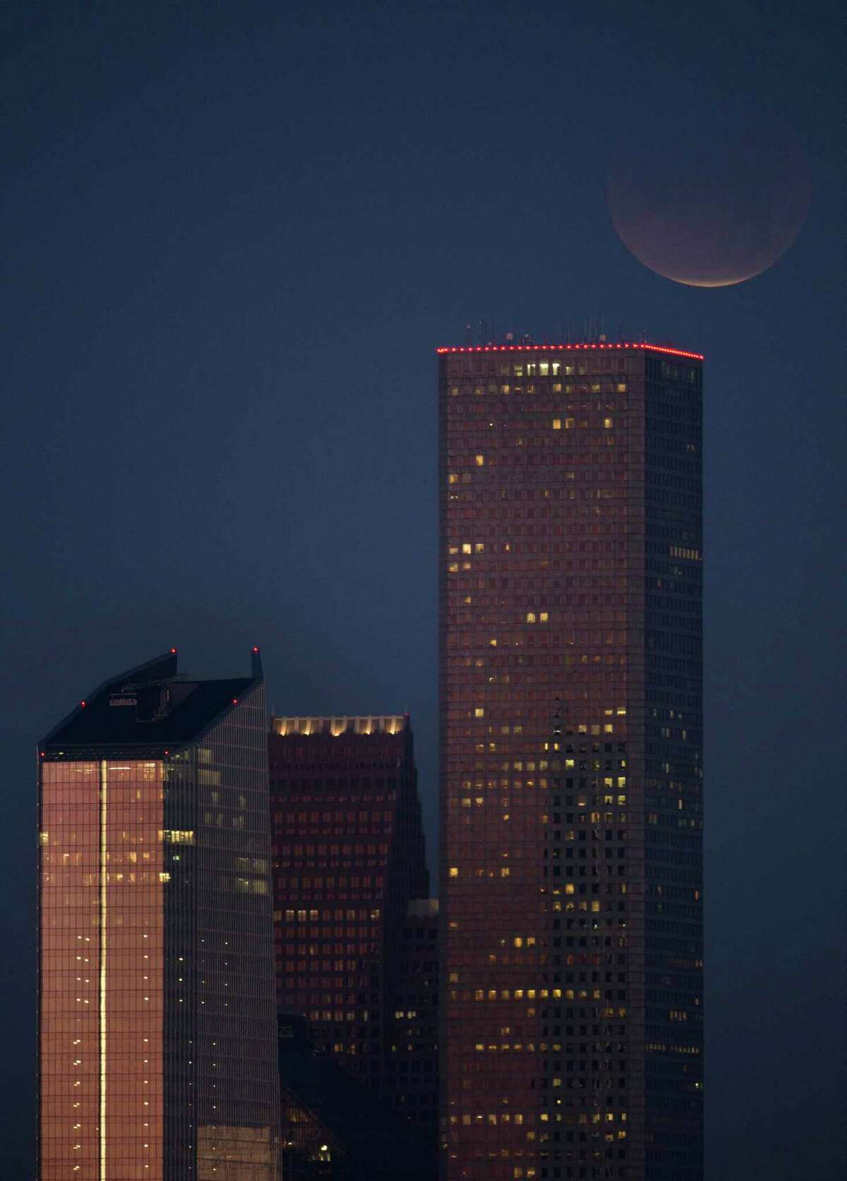 The super blood moon, near full eclipse, seen above downtown Houston Wednesday, Jan. 31, 2018.