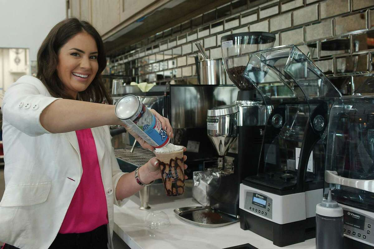 Summer Moon Coffee franchise owner Andrea Baragas puts the finishing touches on an iced latte coffee drink.