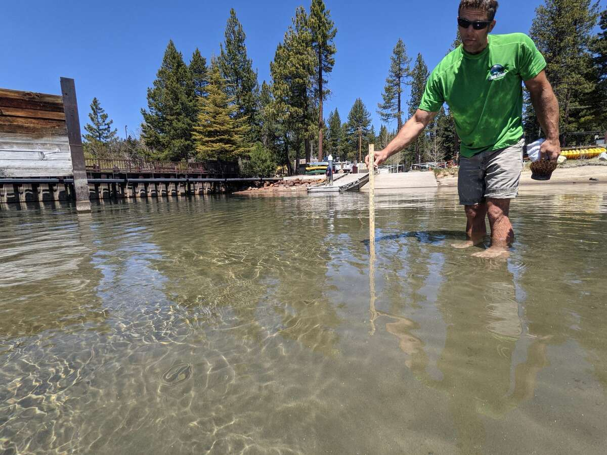 NTPUD Recreation & Parks Department Parks Lead Josh Ramey measures the water depth above the sandbar at the Tahoe Vista Recreation Area boat launch.