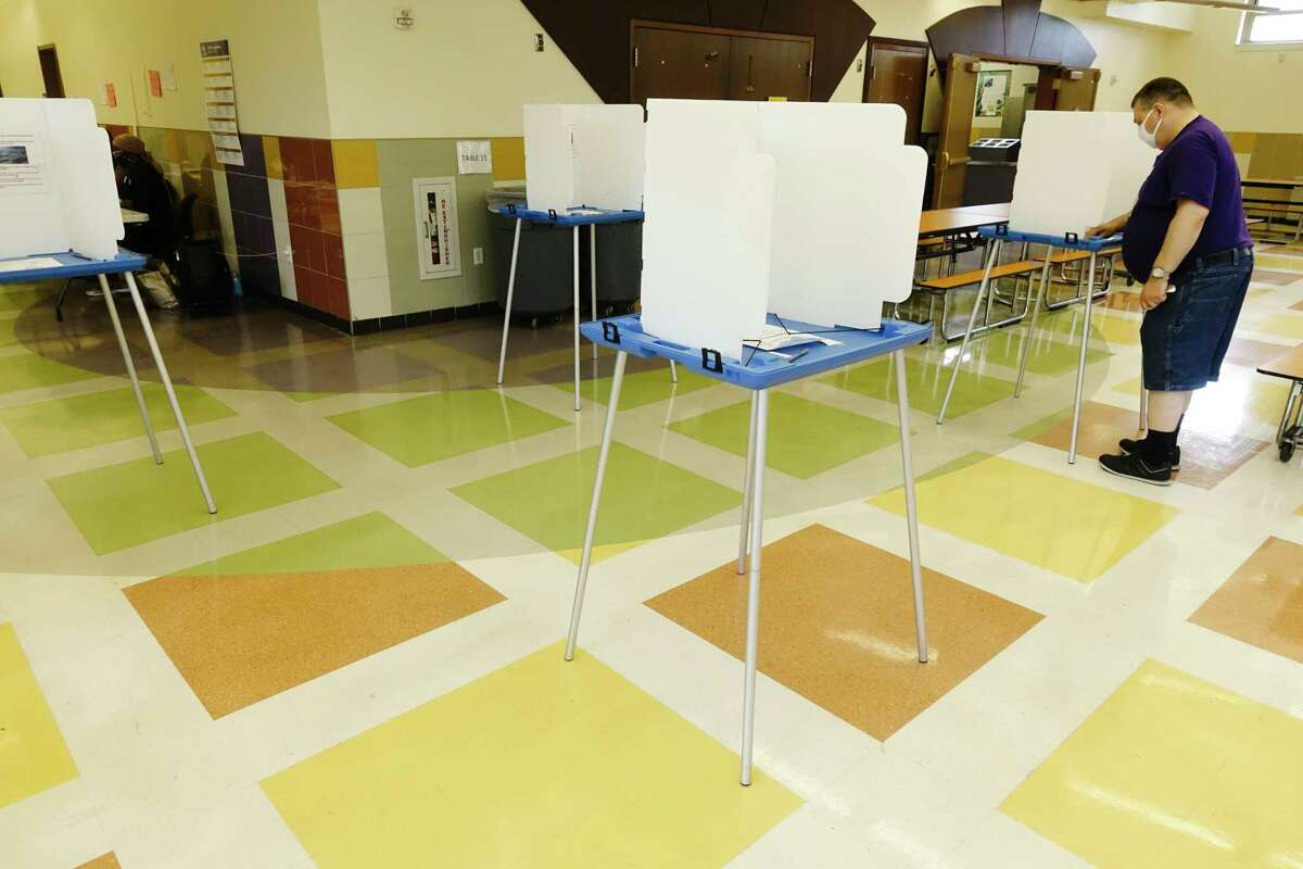 A poll worker cleans one of the voting booths at William S. Hackett Middle School for the school budget vote on Tuesday, May 18, 2021, in Albany, N.Y. (Paul Buckowski/Times Union)