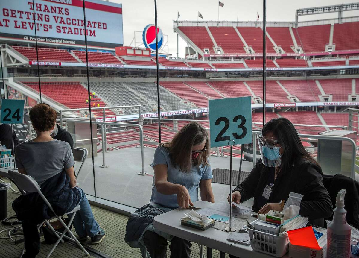 Lynda Barbieri, center, checks in with clinical nurse Lynette Ancheta, right, before recieving her Pfizer COVID-19 vaccine at Levi's Stadium in Santa Clara on Feb. 9, 2021. Santa Clara County advanced Tuesday into the yellow tier, the least restrictive level of California's color-coded pandemic reopening system.
