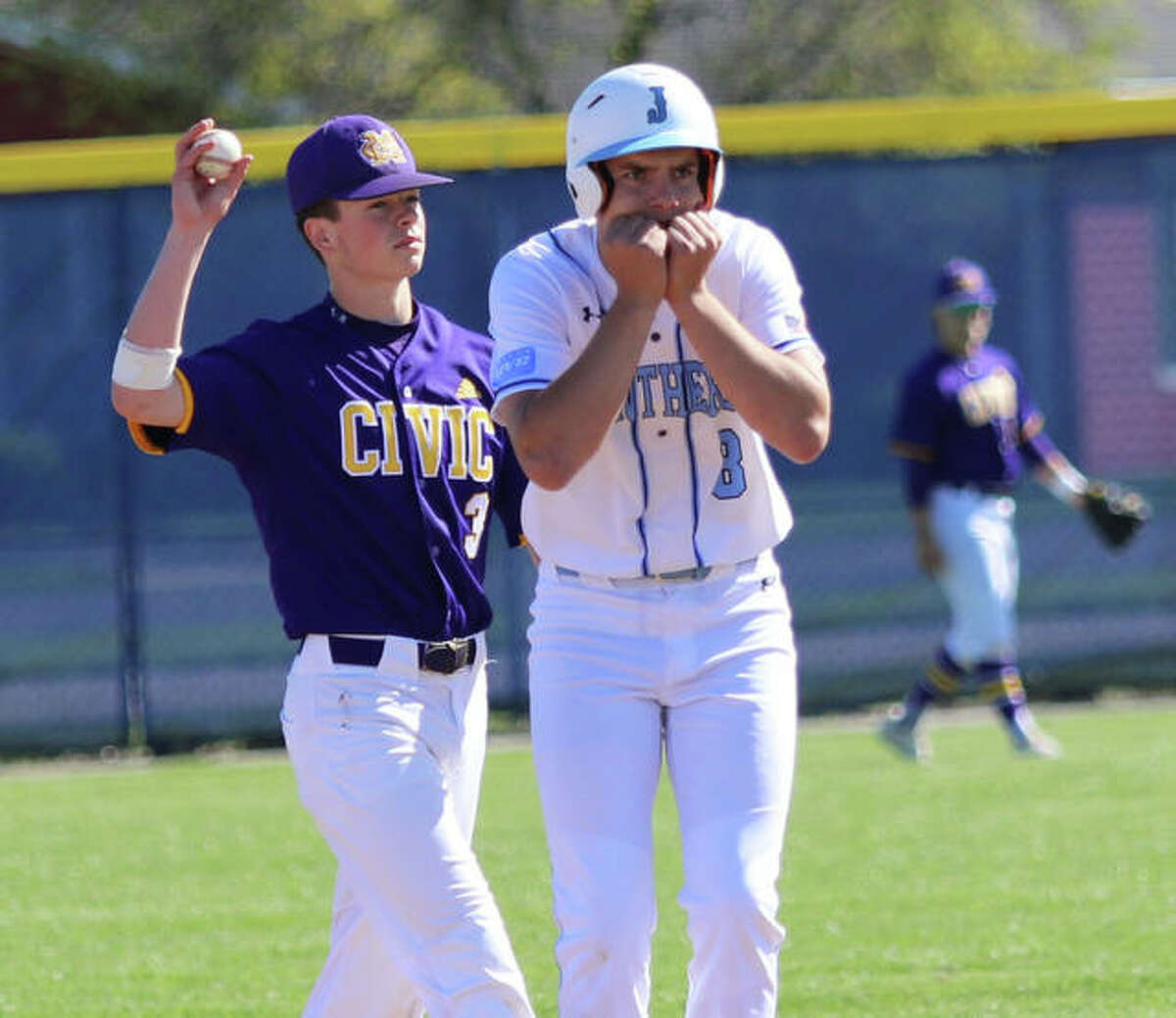 Jersey's Cal Gorman (8) acknowledges the reaction from teammates in the dugout after his double while CM shortstop Luke Parmentier (left) gets the ball back to the pitcher during a MVC baseball game last week in Jerseyville.