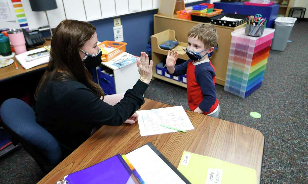 Creekside Forest Elementary School kindergarten math teacher Lindsey Hurst, pictured in February, works with a student at her Tomball ISD campus. Schools across Texas can no longer require mask usage on campus grounds starting June 5.