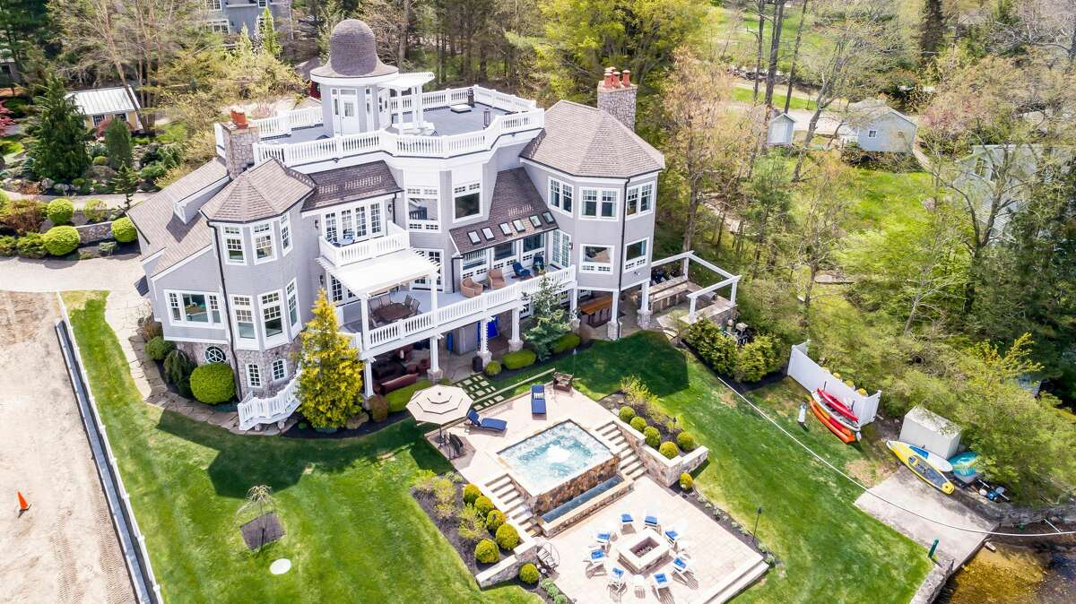 The home at 10 Evans Passway in Morris, Conn. has a full outdoor kitchen complete with a pizza oven, a lounge area with a TV, a Gunite infinity pool and spa, a fire pit and a dock, according to the listing.