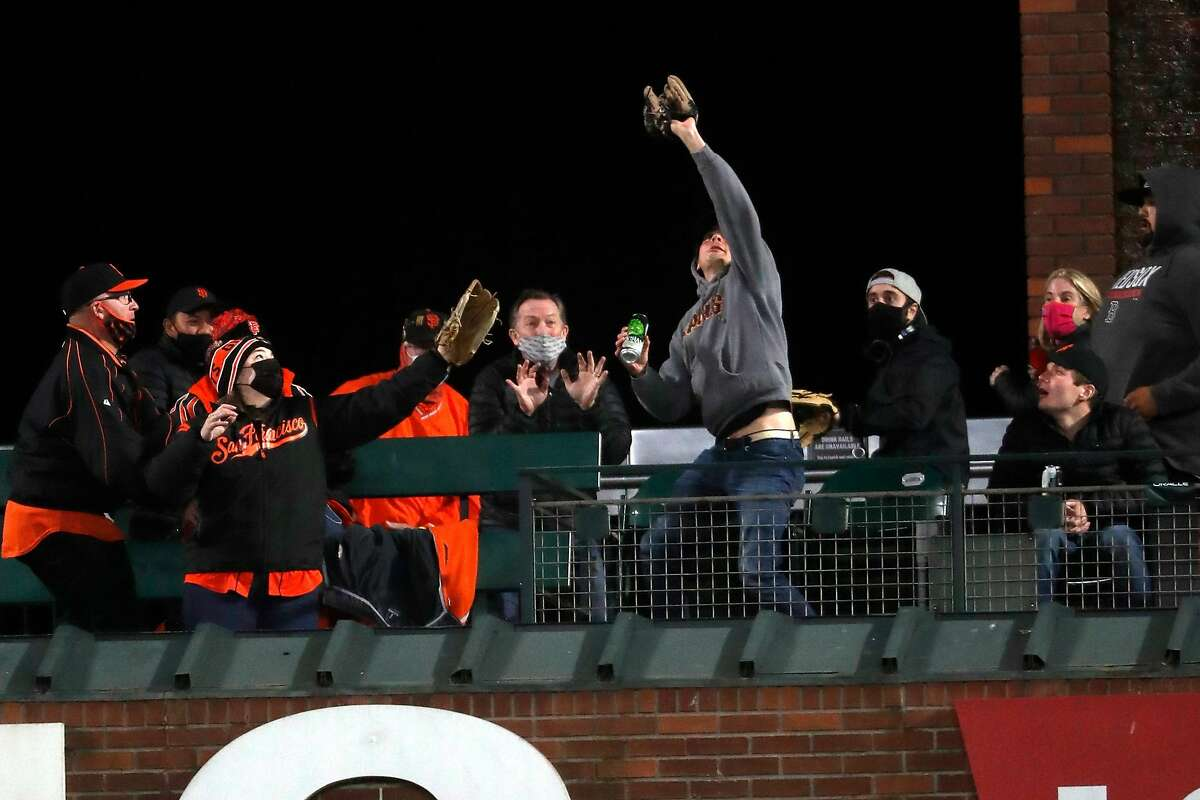 A fan catches San Francisco Giants' Austin Slater's go-ahead solo home run in 7th inning against San Diego Padres at Oracle Park in San Francisco, Calif., on Friday, May 7, 2021.