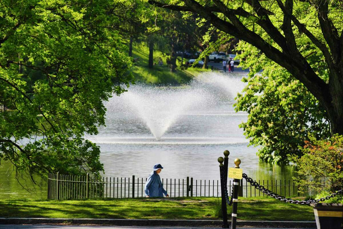 A woman walks around Washington Park Lake on Tuesday, May 18, 2021, in Albany, N.Y. (Paul Buckowski/Times Union)