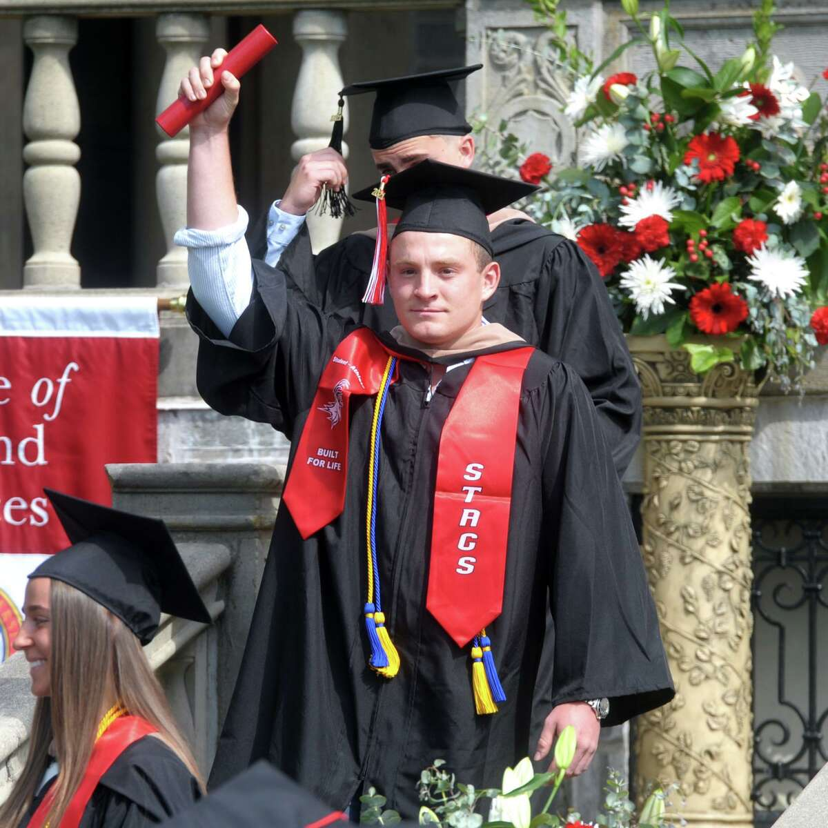 Taylor Strough gestures to the crowd after receiving his diploma during commencement for the Charles F. Dolan School of Business, one of several in-person graduation ceremonies the Fairfield University is holding this week in Fairfield, Conn., May 18, 2021.