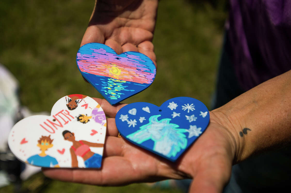 Volunteers work to install small decorated hearts onto the large