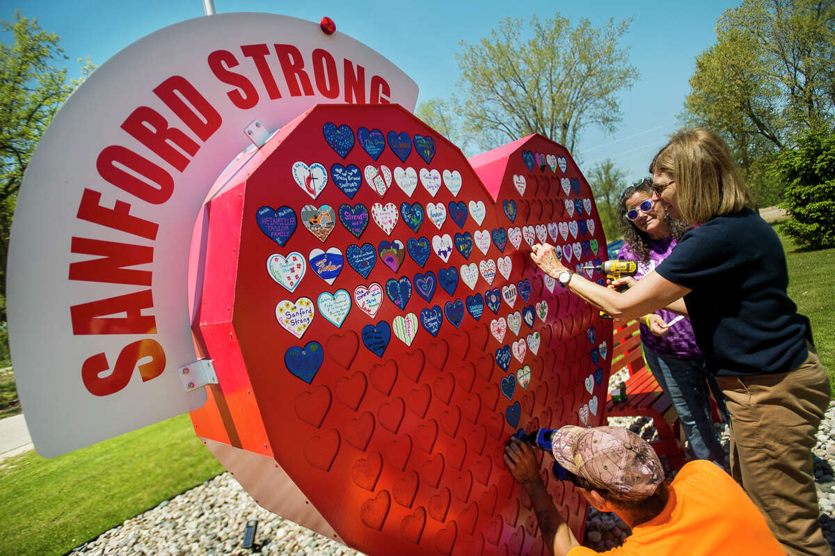 Children's Grief Center Executive Director Camille Gerace Nitschky, center, Midland Area Community Foundation President and CEO Sharon Mortensen, right, and Sanford Department of Public Works Supervisor Steve Rider, bottom, work to install small decorated hearts onto the large