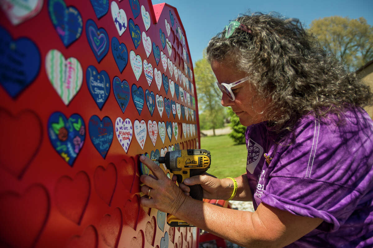 Children's Grief Center Executive Director Camille Gerace Nitschky works to install small decorated hearts onto the large