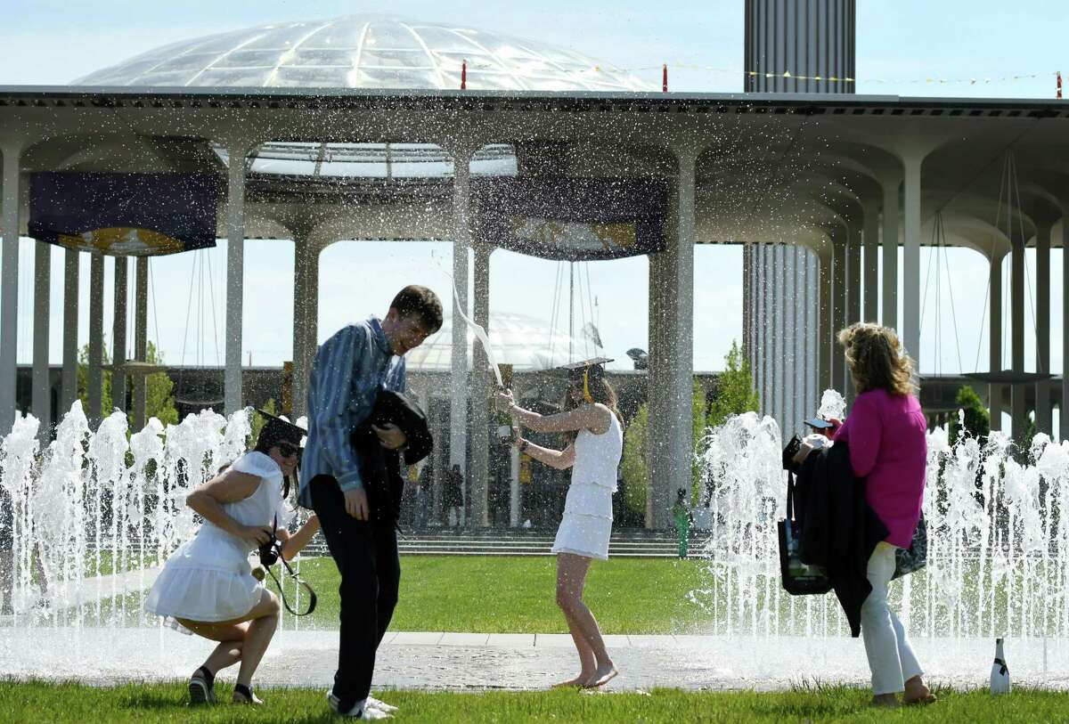 Lauryn Neill of Southampton lets the Champaign spray fly as she celebrates her graduation from the University at Albany on Tuesday, May 18, 2021, in the walk-through fountain at the UAlbany campus in Albany, N.Y. (Will Waldron/Times Union)