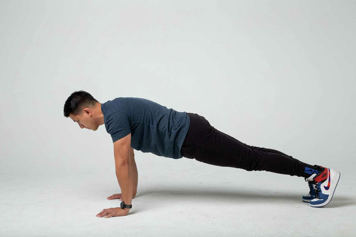Start in a plank, or pushup, position with hands on the ground directly underneath your shoulders and your legs stretched out behind you while you stay on your toes.